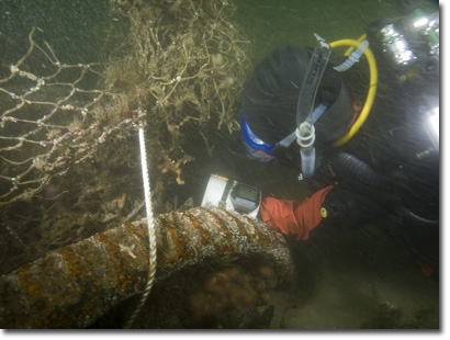 Diver cutting net from wreck