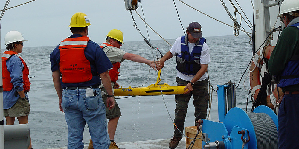 a side scan sonar being deployed off of a ship